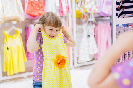 Adorable smiling little girl at the clothes store, try on new yellow summer dress, looking at the mirror.