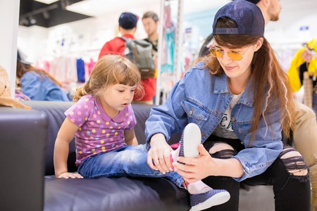 Adorable toddler girl and her mother in children apparel store, buying shoes.