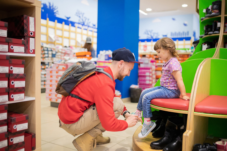 Adorable toddler girl and her father in children apparel store, buying shoes. Фото со стока - 121403232