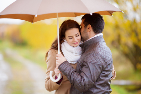 Young couple man and woman under the umbrella, rainy autumn cold day in the park. First date, love, relationships. 版權商用圖片