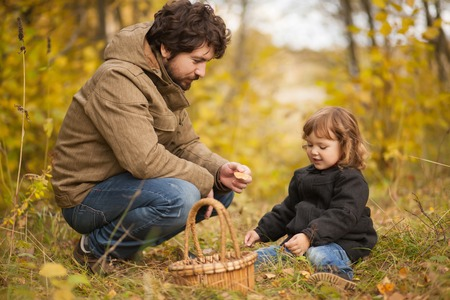 Father and his little daughter together in the wild forest, comunicating, playing, autumn day. Little kid exploring nature.