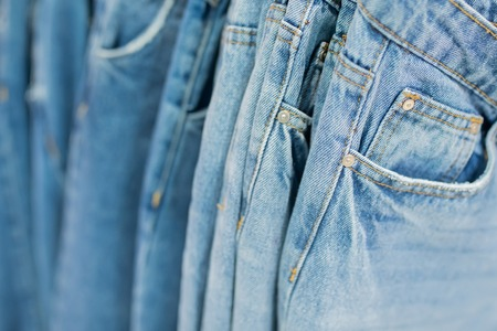 Row of hanged blue jeans in a shop, many models of jeans from different denim.
