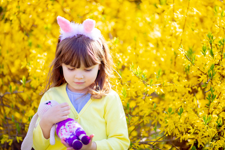 Adorable little funny bunny girl holding rabbit toy in the spring blossom garden, yellow flowers