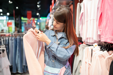 Shopaholic hipster young woman shopping clothes on sale. 版權商用圖片