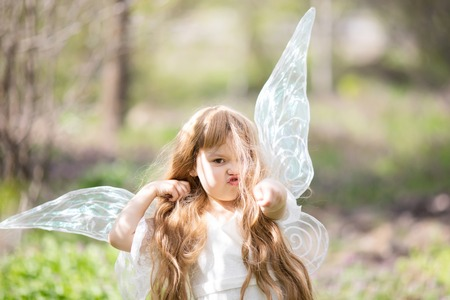 Cute little Angel Fairy girl gets angry and fights. Spring day. Concept of angelic child with a bad temper. Stock Photo