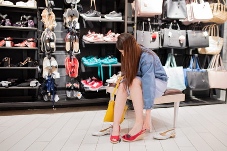 Portrait of a young woman trying on new shoes and bag in a shoe shop.