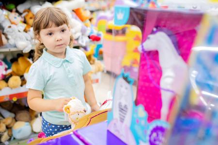Little kid girl having fun at the children shop, choosing toys, lifestyle.