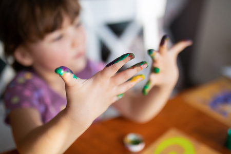Cute little preschool gir having fun, looking at her painted hands and smiling. Education, school, art and painitng concept.