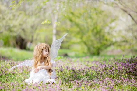 Fairy tale concept. Little toddler girl wearing beautiful princess dress with fairy wings in the forest or park, spring day, white blooming trees.