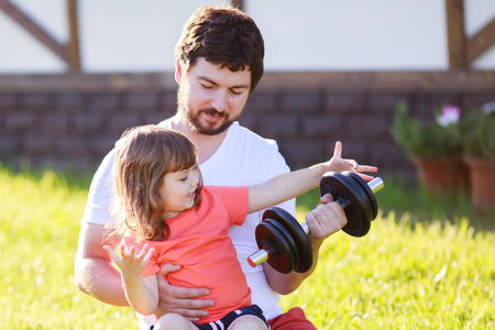 Happy little girl and her father lifting dumbbells putdoors. Active healthy life for family. Fitness. Sport for little children.