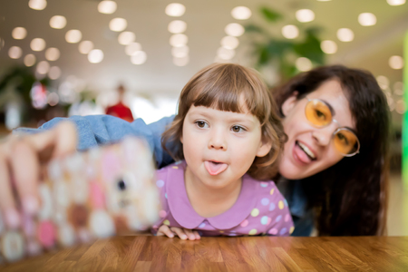 Mother abd her adorable daughter hsving fun making selfie together, lifestyle.