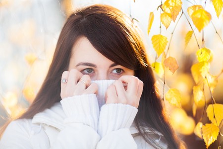 Attractive young woman with beautiful big eyes on a cold sunny autumn day, fall outdoors, closeup portrait, copy space.