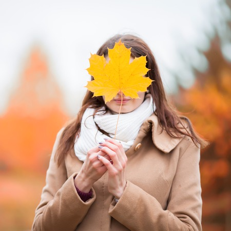 A cheerful woman hides her face behind an autumn yellow maple leaf, close-up.