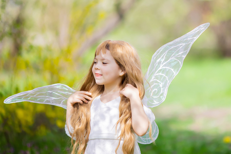 Portrait of cute little curly blonde Angel Fairy girl smiles and teases. Spring day. Concept of angelic child with a bad temper.