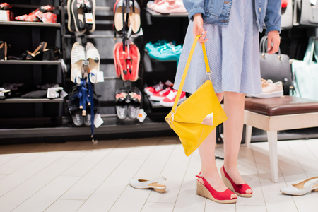 Portrait of a young woman trying on new shoes and bag in a shoe shop. 版權商用圖片 - 124745978