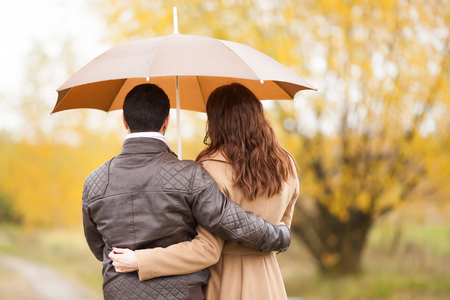 Young couple man and woman under the umbrella, rainy autumn cold day in the park. First date, love, relationships. 版權商用圖片 - 124745979
