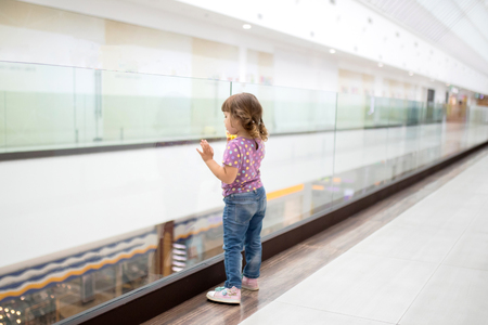 Little girl alone in shopping mall center, looking for her mother. The child was lost in the big store.