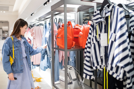 Shopaholic hipster young woman shopping clothes on sale. 版權商用圖片 - 124745981
