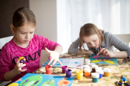Two sisters little girls drawing with fingers on paper at home. Play, fun, childhood. Montessori school.