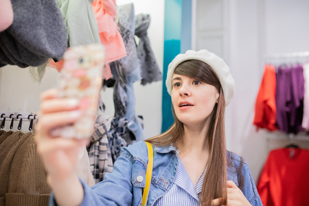 Young woman trying on new beret hat at the clothes store, making selfie. 版權商用圖片 - 124745985