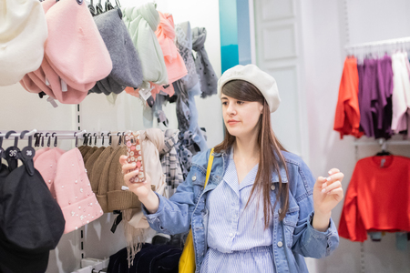 Young woman trying on new beret hat at the clothes store, making selfie. 版權商用圖片