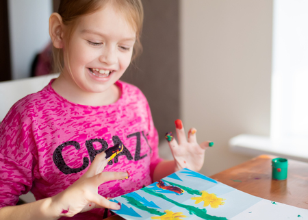 Adoranle little girl s drawing with fingers on paper at home. Play, fun, childhood. Montessori school. 版權商用圖片