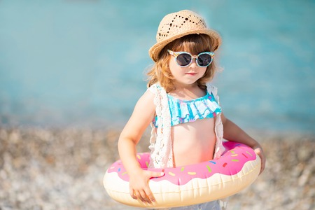 Adorable little girl wearing sunglasses, inflatable over-sleeves floats and inflatable donut float ring, beach 版權商用圖片 - 124745948