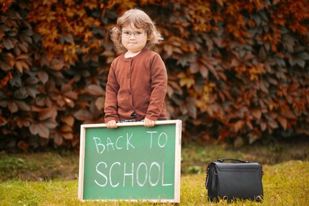 Cute toddler girl wearing glasses and school uniform with back to school blackboard.
