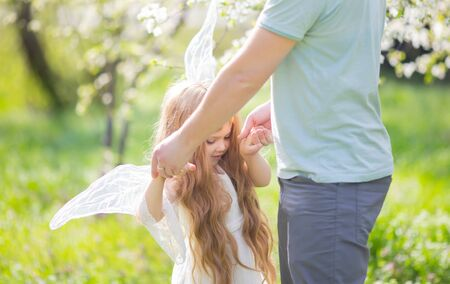 Outdoor ortrait of a happy father and a beautiful little girl wearing angel costume, Fathers day. Stock Photo
