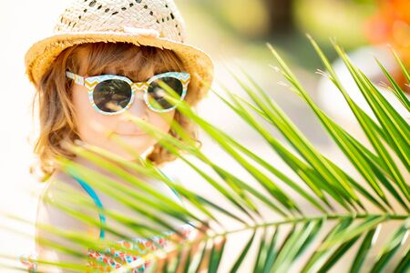 Adorable little girl wearing sunglasses, walking at the tropical resort, hiding behind the palm three at the sunny summer day. 版權商用圖片