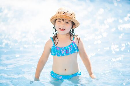 Adorable toddler girl having fun at the water park (aquapark).