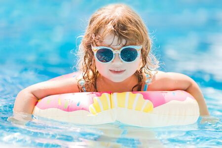 Little girl in swimming pool on funny inflatable donut float ring, learning how to swim.