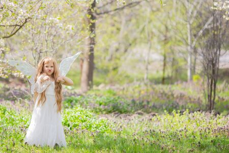 Cute little Angel Fairy girl gets angry and fights (doing karate). Spring day. Concept of angelic child with a bad temper or girl taking karate. 版權商用圖片 - 124745856