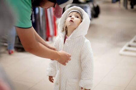 Father helps his adorable little girl with trying new coat for fall or winter during shopping. Warm clothes for child.