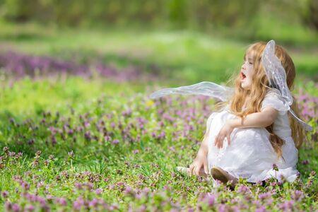 Cute little fairyangel child sneezing because of allergies at the beautiful flower field in spring.