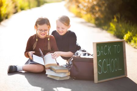 Adorable old-fashioned happy little 6 years old and 10 years old girls reading and smiling,  back to school chalkboard.