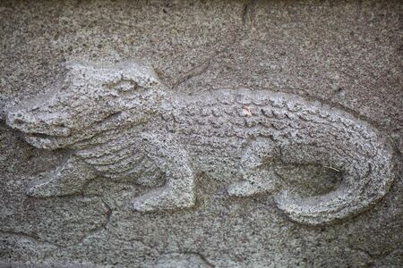 Crocodile carved in stone on the wall, old decorative ornament.