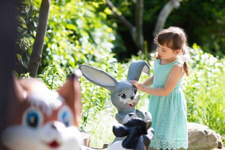 Little gir exploring statue of cute little rabbit. Concept of childhood and fairytales of the animals.