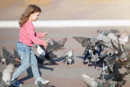 Little girl running, flaunts the pigeons on the street in town. Happy childhood. 版權商用圖片 - 124745869
