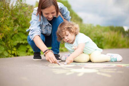 Little girls chalking at the asphalt with elder sister or nanny.