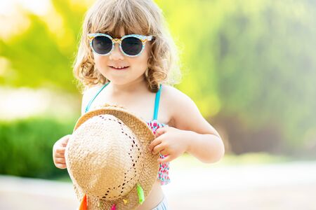 Adorable little girl wearing sunglasses and straw hat, walking at the tropical resort, palm trees