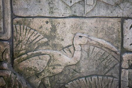 Heron carved in stone on the wall, old decorative ornament.