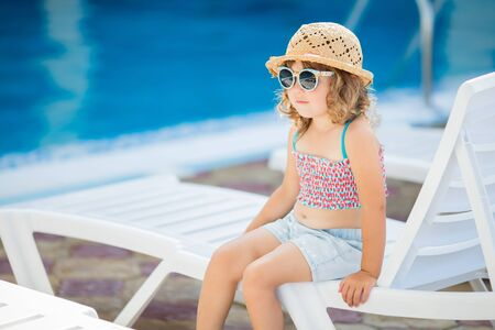 Adorable little girl wearing straw hat and sunglasses sitting near the swimming pool, summer day.