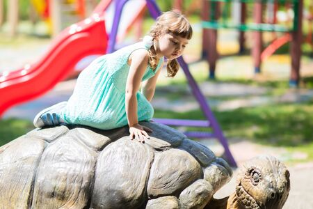 Adorable little girl in the zoo, sitting on the giant turtle statue