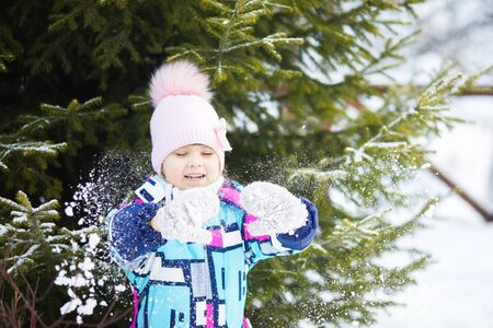 Cute little girl outdoors on a sunny winter day, having fun, playing snowballs, snowy day