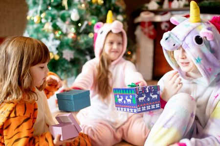 Happy little kids wearing kigurumi pajamas at Christmas eve. Three sisters in unicorn and tiger costumes opening presents in beautiful living room decorated for Xmas with traditional fire place..