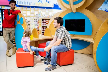 Adorable toddler girl and her father in children apparel store, buying shoes.
