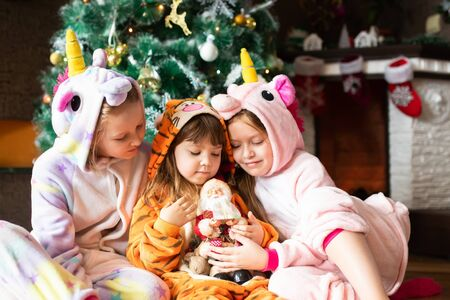 Happy little kids wearing kigurumi pajamas at Christmas eve. Three sisters in unicorn and tiger costumes siting in beautiful living room decorated for Xmas with traditional fire place. Archivio Fotografico