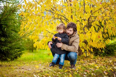 Father and daughter walking together in the park, fall day. Little girl and her dad exploring nature outdoors. Colorful autumn foliage. Copyspace Archivio Fotografico