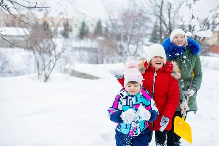 Three little girls sisters playing snowballs, having fun on a sunny snowy day, winter activity for kids